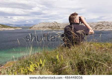 Man in black T-shirt sitting in grass on top of island on sunny day, looking around with binoculars. Helgeland archipelago, Norway.
