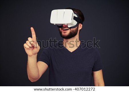 Man in black t-shirt touch something with his right hand using virtual reality glasses, on black background - stock photo