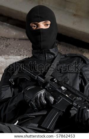 Man in black uniform holding M-4 rifle - stock photo