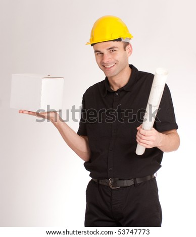 Man in black wearing a yellow safety helmet, rolled up blueprints and a white box - stock photo