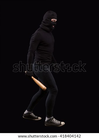 Man in black with black mask on. Burglar going to steak something or someone. Man holding bat over black background. Isolated on black. - stock photo