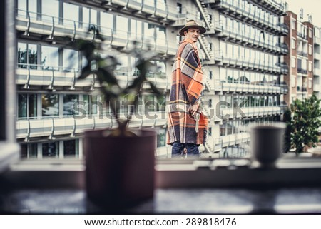 Man in blanket on multifamily house background. - stock photo