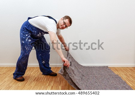 Man in blue overall spreads Painters blanket