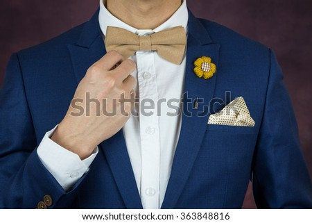 Man in blue suit with coffee cream bowtie color, flower brooch, and dot pattern handkerchief, close up, adjusting bowtie
