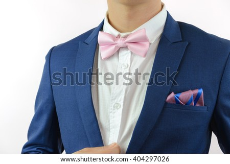 Man in blue suit with pink bow tie, flower brooch, and pink blue strip pocket square, close up