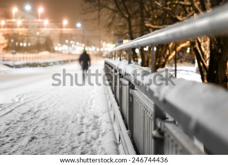 Man in blurred motion walking in city in winter evening - stock photo
