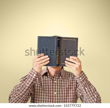 Man in brown plaid shirt reading a book - stock photo