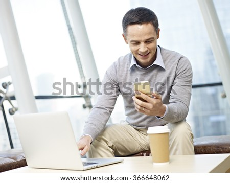 man in business casual wear looking at cellphone while using laptop computer in office. - stock photo