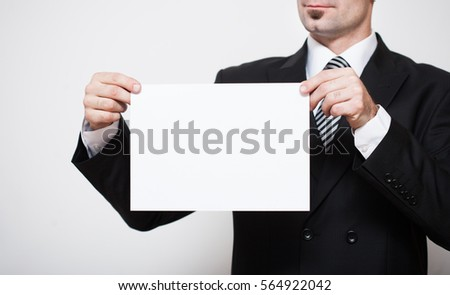 Man in business suit holding white paper in hands. Free space for your text