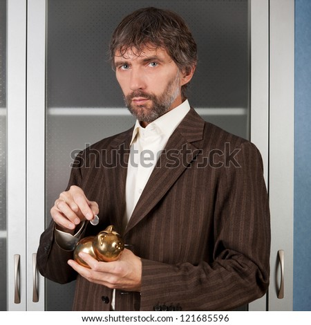 man in business suit puts coin in a piggy bank - stock photo