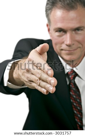 Man in business suite offering his hand in a posture of greeting or agreement. - stock photo