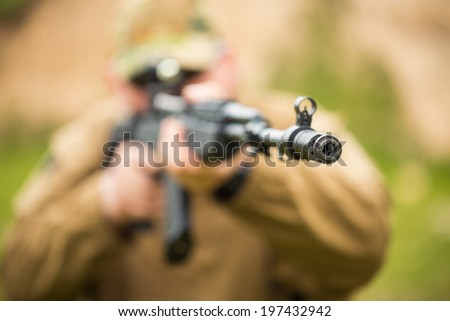 Man in camouflage with a shotgun aiming at a target. Focus on hole, small DOF - stock photo