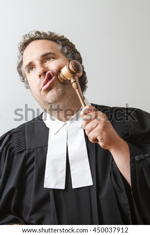 Man in canadian lawyer robe slamming a gavel on his face - stock photo