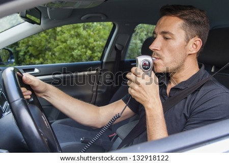Man in car blowing into breathalyzer - stock photo