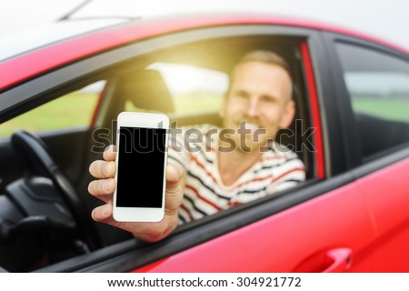 Man in car showing smart phone display smiling happy. Focus on mobile phone. - stock photo