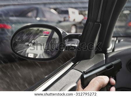 man in car with gun police car in sideview mirror - stock photo