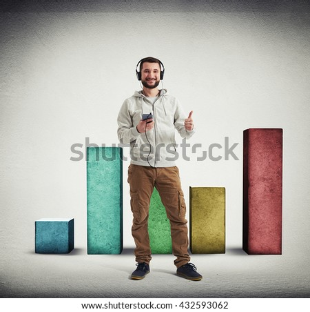 Man in casual clothes and headphones is showing a thumb up gesture with big square colorful columns of different height standing behind him on white background with vignette - stock photo