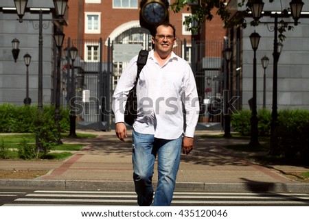 Man in casual dress crossing the road with classic English building on background