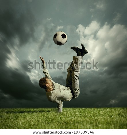 Man in casual suit kick football ball over head - stock photo