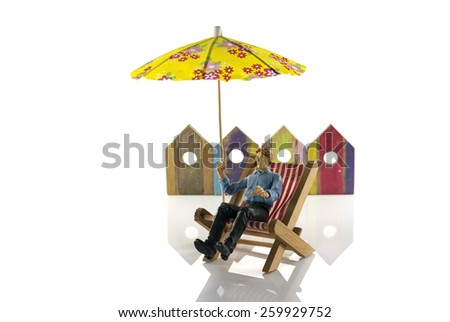 man in chair on the beach with beachhouses as background - stock photo