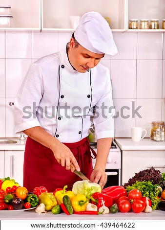 Man in chef hat keeps knife and cooking fresh vegetable salad. There are vegetable on foreground. Vegetarian cooking. - stock photo