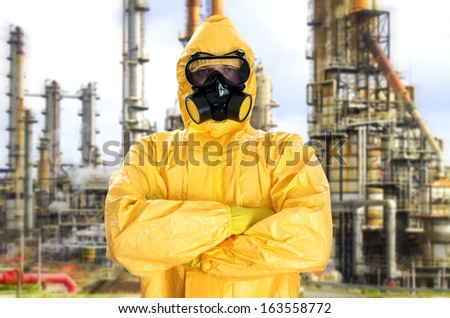 Man in chemical protective suit over factory - stock photo