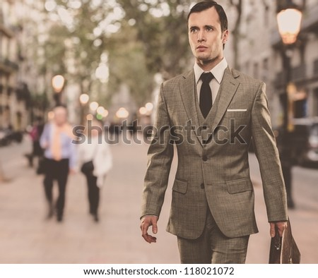 Man in classic grey suit with briefcase walking outdoors - stock photo