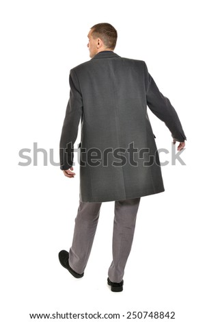 Man in coat looking out for something ,full length ,back view on a white background - stock photo