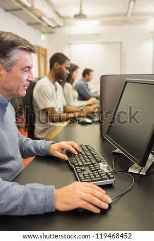 Man in computer class in college - stock photo