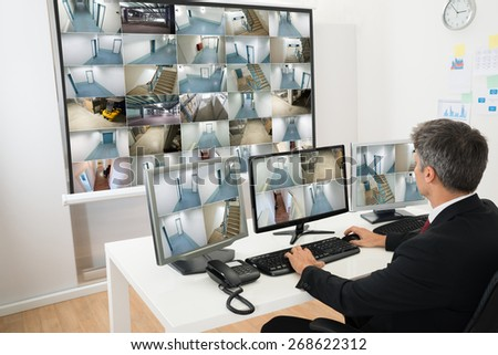 Man In Control Room Monitoring Multiple Cctv Footage - stock photo