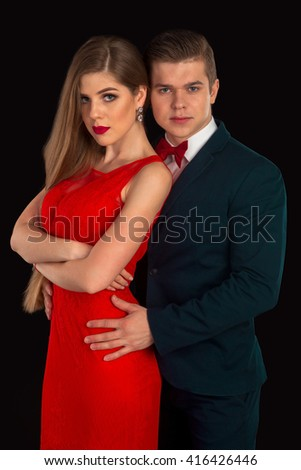 Man in costume and woman in red dress are posing
