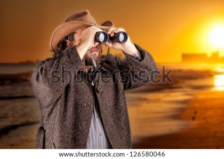 Man in cowboy hat looking through binoculars - stock photo