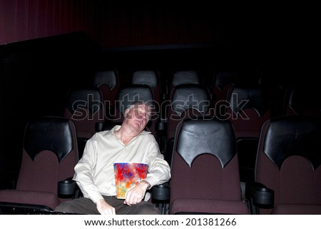Man in empty movie theater asleep in his seat