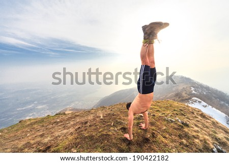 man in equilibrium in the top of the mountain - stock photo