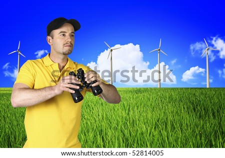 man in field and blue cloudy sky background with power wind station - stock photo