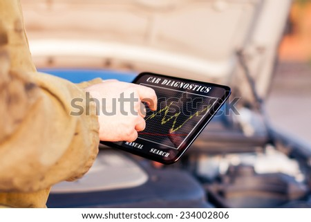 Man in Front of a Car using Digital Tablet - stock photo