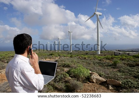 man in front of a computer phoning next to wind turbines