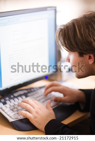 Man in front of computer screen. Shallow dof focus on hand. - stock photo