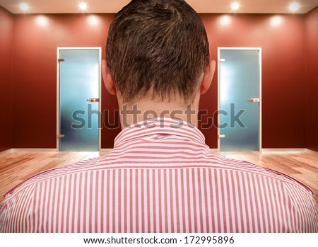 Man in front of two doors - stock photo