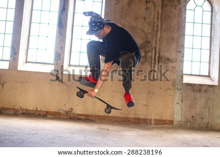 Man in gangster mask with skateboard.