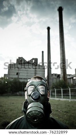 man in gas mask on smoky industrial background with pipes - stock photo