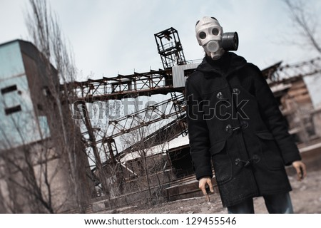 Man in gas mask standing at the factory after doomsday - stock photo