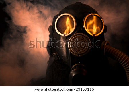 Man in gas mask with fire reflection in the eyes - stock photo