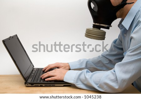 Man in gas mask working on his laptop - stock photo