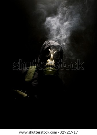 Man in gasmask with abstract smoke - stock photo