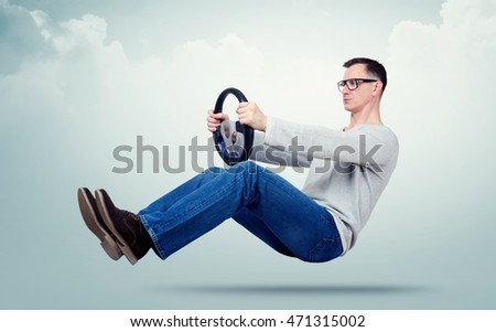 Man in glasses drives a car with a steering wheel