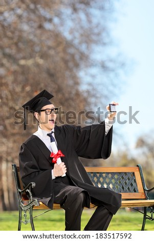 Man in graduation gown taking a selfie in park  - stock photo