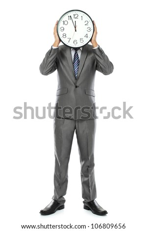 man in gray suit holding big clock covering his face. isolated over white background - stock photo