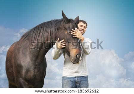 man in gray t-shirt hugging  black horse  - stock photo