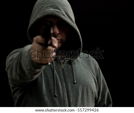 Man in green hoodie points gun